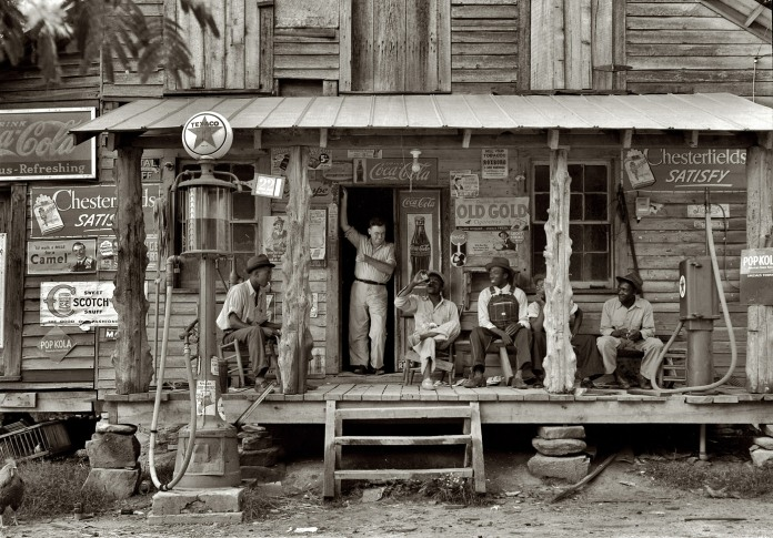 """July 1939. Gordonton, N.C. """"Country store on dirt road. Sunday afternoon. Note kerosene pump on the right and the gasoline pump on the left. Rough, unfinished timber posts have been used as supports for porch roof. Negro men sitting on the porch. Brother of store owner stands in doorway."""""""