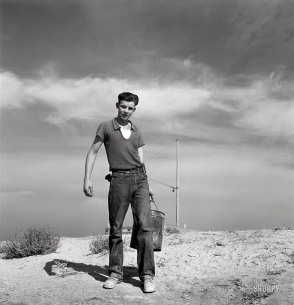 """October 1939. """"Dazey farm. Seventeen year old boy going to feed the pigs. Homedale district, Malheur County, Oregon."""""""
