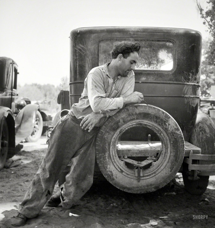 """October 1935. Marysville, California. """"Agricultural worker in migrant camp figuring his year's earnings,"""" i.e. a rubber check."""